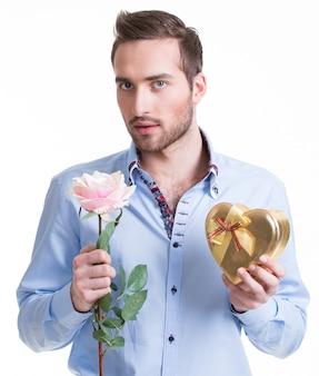 Młody przystojny mężczyzna z różową różą i prezentem - na białym tle