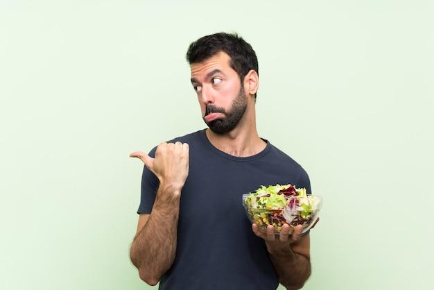 Młody przystojny mężczyzna z sałatką nad odosobnioną zieleni ścianą nieszczęśliwą i wskazuje z boku