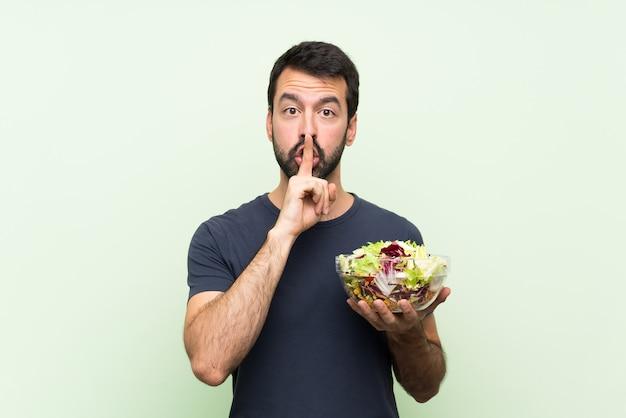 Młody przystojny mężczyzna z sałatką nad odosobnioną zieleni ścianą pokazuje znak cisza gesta kładzenia palec w usta