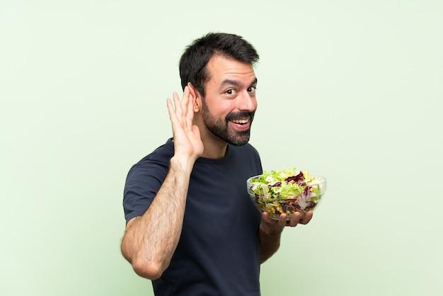 Młody przystojny mężczyzna z sałatką nad odosobnioną zieleni ścianą słucha coś stawiając rękę na ucho