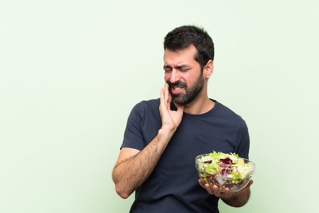 Młody przystojny mężczyzna z sałatką nad odosobnioną zieleni ścianą z bólem zęba