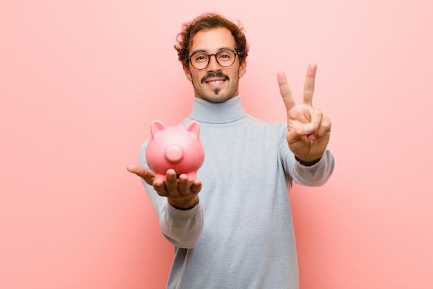 Młody przystojny mężczyzna z skarbonka przeciw różowej płaskiej ścianie