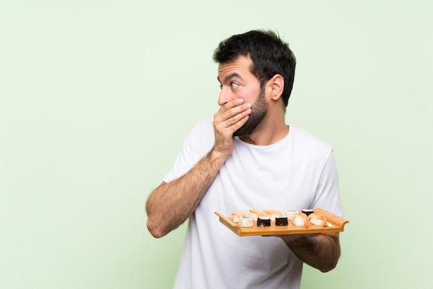 Młody przystojny mężczyzna z sushi na pojedyncze zielone ściany obejmujące usta i patrząc z boku