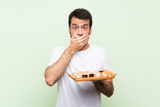 Młody przystojny mężczyzna z sushi na pojedyncze zielone ściany obejmujące usta rękami