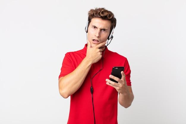 Młody przystojny mężczyzna z szeroko otwartymi ustami i oczami i ręką na brodzie ze smartfonem i zestawem słuchawkowym