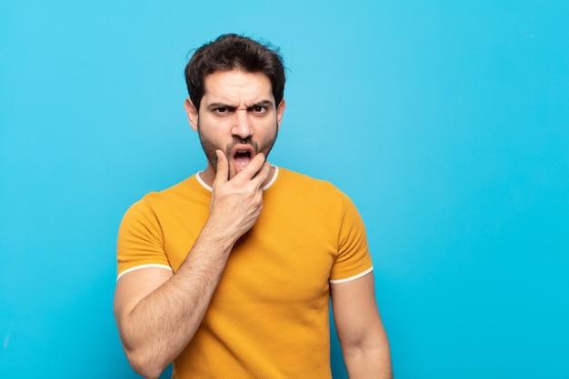 Młody przystojny mężczyzna z szeroko otwartymi ustami i oczami oraz ręką na brodzie, czuje się nieprzyjemnie zszokowany, mówi co lub wow