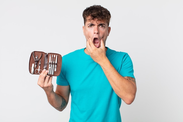 Młody przystojny mężczyzna z szeroko otwartymi ustami i oczami, ręką na brodzie i trzymającym walizkę z narzędziami do paznokci