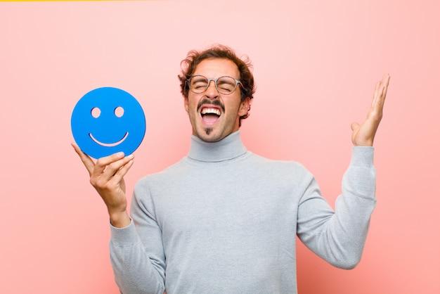 Młody przystojny mężczyzna z uśmiechniętą twarzą na różowej płaskiej ścianie