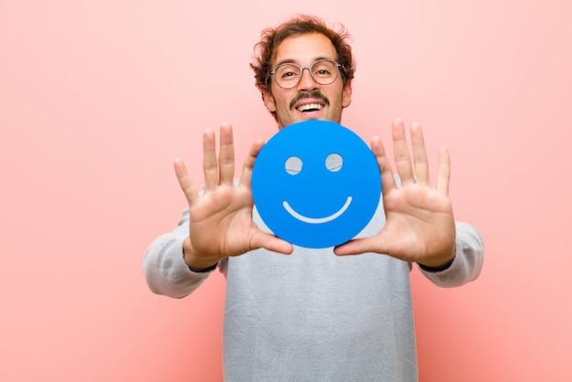 Młody przystojny mężczyzna z uśmiechniętą twarzą przeciw różowej płaskiej ścianie
