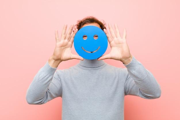 Młody przystojny mężczyzna z uśmiechniętą twarzą przeciw różowemu mieszkaniu