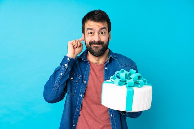 Młody przystojny mężczyzna z wielkim tortem na pojedyncze niebieskie ściany sfrustrowane i obejmujące uszy