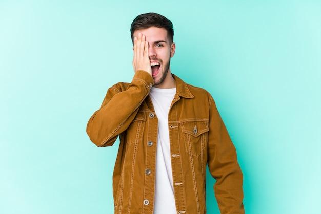 Młody przystojny mężczyzna zabawy obejmujące połowę twarzy z dłoni.