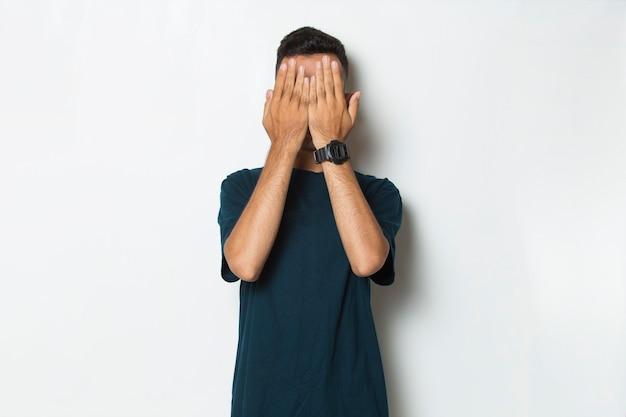 Młody przystojny mężczyzna zakrywa twarz rękami na białym tle