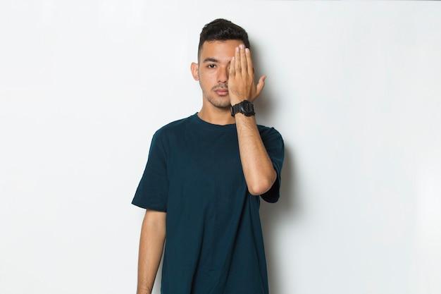 Młody przystojny mężczyzna zakrywający jedno oko ręką na białym tle