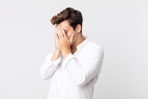 Młody przystojny mężczyzna zakrywający oczy dłońmi ze smutnym, sfrustrowanym wyrazem rozpaczy, płaczu, widoku z boku