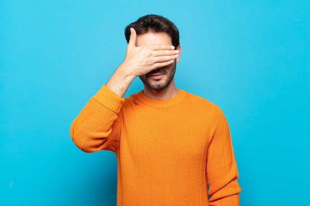 Młody przystojny mężczyzna zakrywający oczy jedną ręką, czując strach lub niepokój, zastanawiając się lub na ślepo czekając na niespodziankę