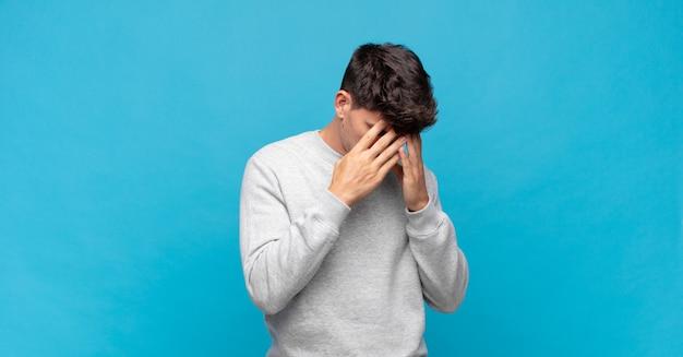 Młody przystojny mężczyzna zakrywający oczy rękami ze smutkiem