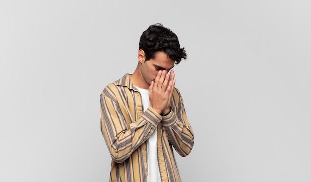 Młody przystojny mężczyzna zakrywający oczy rękami ze smutnym, sfrustrowanym spojrzeniem rozpaczy, płacz, widok z boku