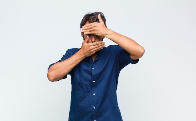Młody przystojny mężczyzna zakrywający twarz obiema rękami