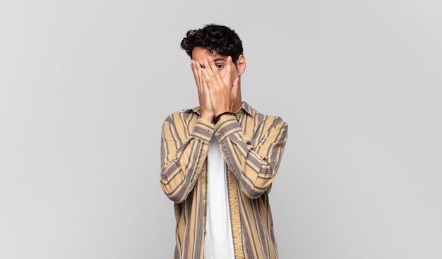 Młody przystojny mężczyzna zakrywający twarz rękami, zaglądający między palce z zaskoczonym wyrazem i patrząc w bok