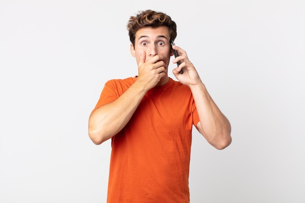 Młody przystojny mężczyzna zakrywający usta dłońmi w szoku i rozmawiający ze smartfonem