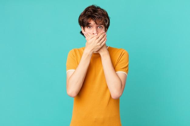 Młody przystojny mężczyzna zakrywający usta dłońmi w szoku