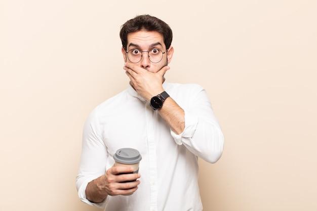 """Młody przystojny mężczyzna zakrywający usta dłońmi ze zszokowanym, zaskoczonym wyrazem twarzy, dochowujący tajemnicy lub mówiący """"ups"""""""