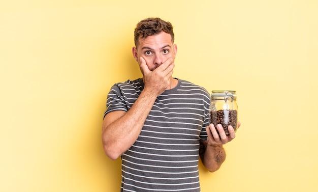 Młody przystojny mężczyzna zakrywający usta rękami z szokującą koncepcją ziaren kawy