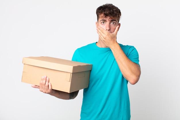 Młody przystojny mężczyzna zakrywający usta rękami zszokowanym i trzymającym kartonowe pudełko
