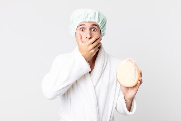 Młody przystojny mężczyzna zakrywający usta rękami zszokowanym szlafrokiem, czepkiem i gąbką