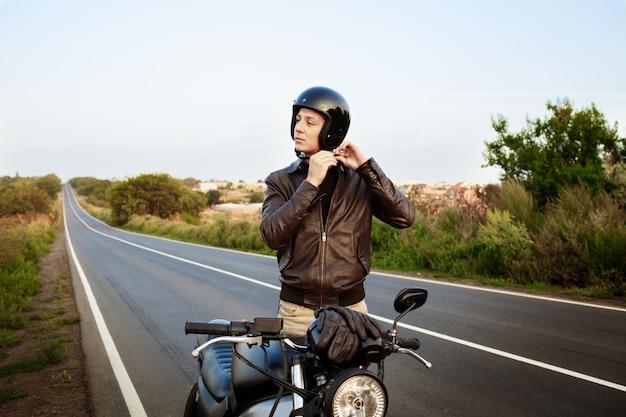 Młody przystojny mężczyzna zapinany na kask, stojący w pobliżu swojego motocykla.