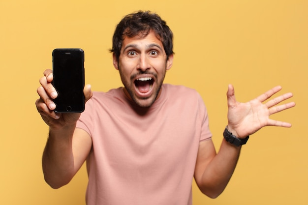 Młody przystojny mężczyzna zaskoczony koncepcja smartfona wyrażenie