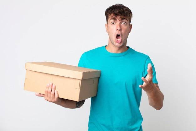 Młody przystojny mężczyzna zdumiony, zszokowany i zdumiony niewiarygodną niespodzianką i trzymający kartonowe pudełko