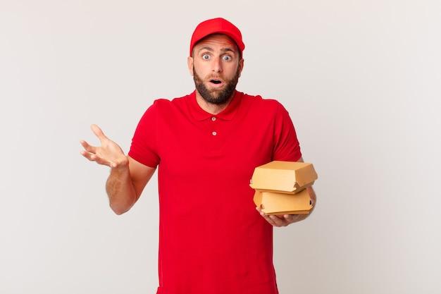 Młody przystojny mężczyzna zdumiony, zszokowany i zdumiony niewiarygodną niespodzianką, która dostarcza burgera z niespodzianką