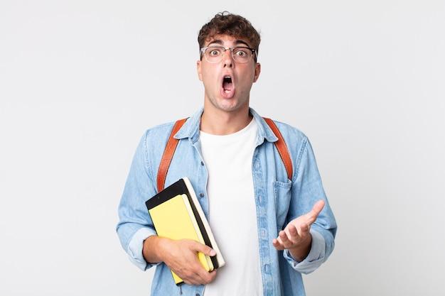 Młody przystojny mężczyzna zdumiony, zszokowany i zdumiony niewiarygodnym zaskoczeniem. koncepcja studenta uniwersytetu