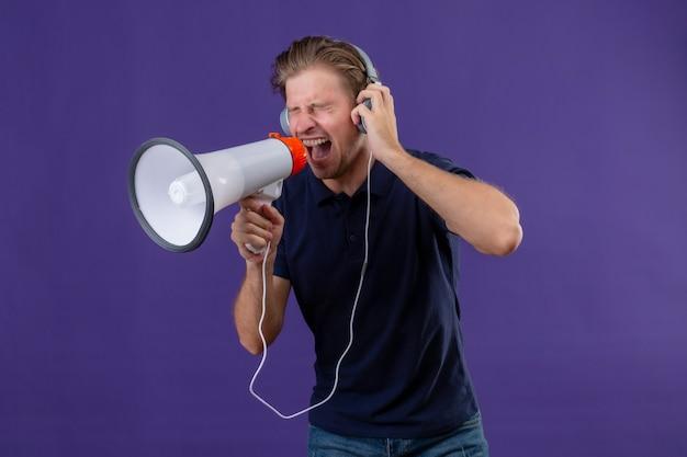 Młody przystojny mężczyzna ze słuchawkami krzycząc przez megafon stojący na fioletowym tle