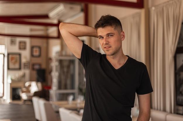 Młody przystojny mężczyzna ze stylową fryzurą z uroczym uśmiechem w modnej czarnej koszulce pozuje stojąc w kawiarni vintage w mieście. europejski model współczesnego faceta w pomieszczeniu.