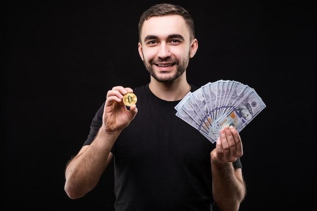 Młody przystojny mężczyzna ze złotym bitcoinem i gotówką dolara w drugiej ręce na czarnym tle