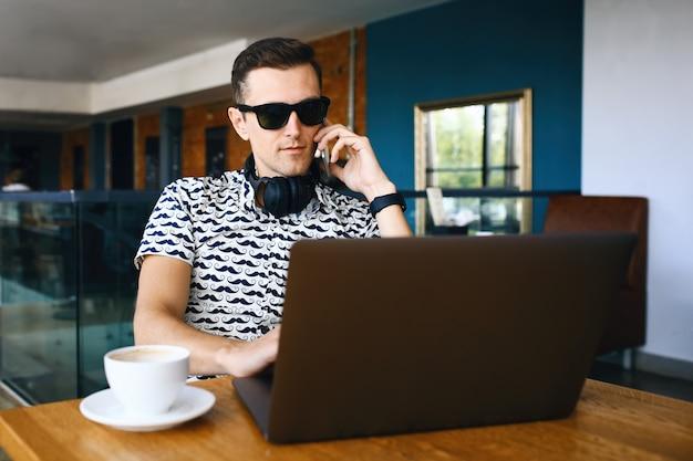 Młody przystojny modnisia mężczyzna w okularach przeciwsłonecznych używa laptop, opowiada telefon komórkowego w stołówce.