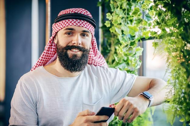 Młody przystojny modny brodaty muskularny arab facet stojący obok okna w kawiarni, trzymając inteligentny telefon