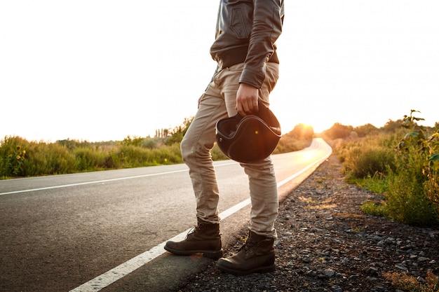 Młody przystojny motocyklisty mienia hełm, pozuje przy wsi drogą.