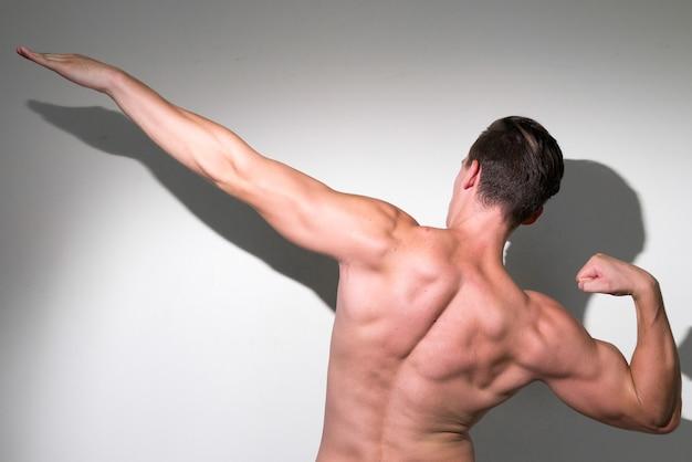 Młody przystojny muskularny mężczyzna z brązowymi włosami bez koszuli