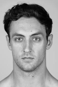 Młody przystojny muskularny mężczyzna z falowanymi włosami bez koszuli na białym tle w czerni i bieli
