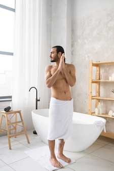 Młody przystojny muskularny mężczyzna z miękkim białym ręcznikiem na biodrach stojący na podłodze łazienki po gorącej kąpieli z pianką