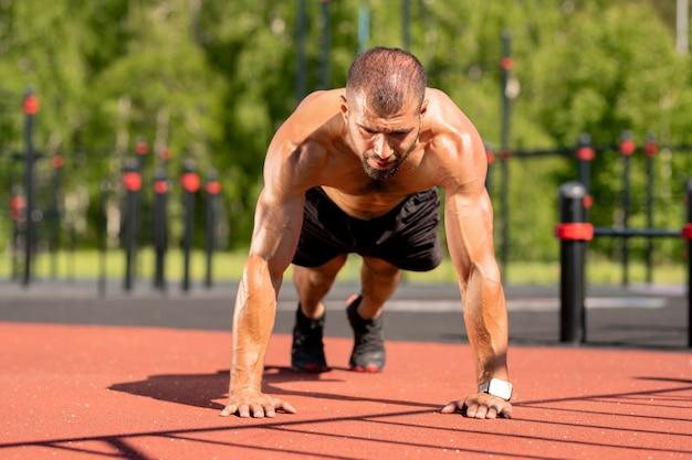 Młody przystojny muskularny sportowiec robi pompki, stojąc na nogach i rękach na boisku sportowym na świeżym powietrzu
