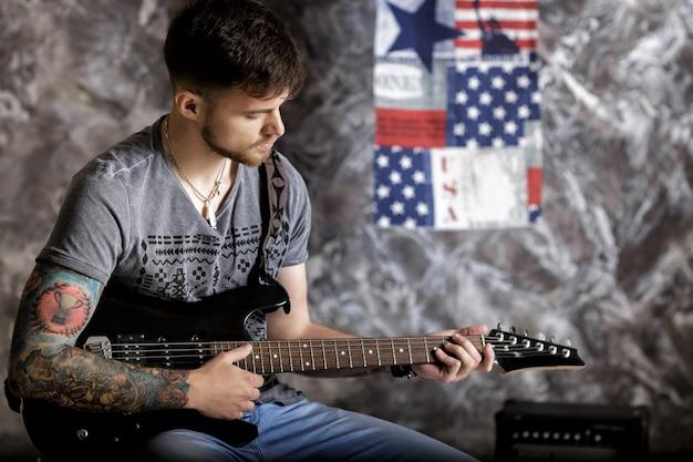 Młody przystojny muzyk grający na gitarze elektrycznej na ciemnym tle