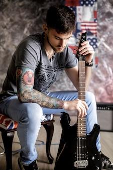 Młody przystojny muzyk z gitarą elektryczną na ciemnym tle