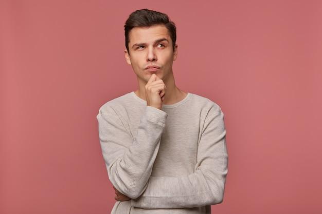 Młody przystojny myślący facet nosi kraciastą koszulę, patrzy i dotyka brodę, myśli o nowym samochodzie, odizolowanym na różowym tle.