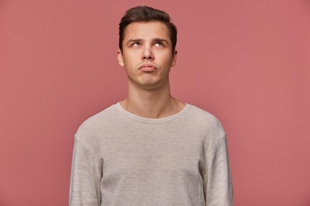 Młody przystojny myślący facet nosi w kraciastej koszuli, patrzy i dotyka brodę, wygląda na znudzonego, odizolowany na różowym tle.