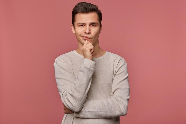 Młody przystojny myślący facet ubrany w kraciastą koszulę, patrzy w kamerę i dotyka brody, myśli o czymś, odizolowany na różowym tle.